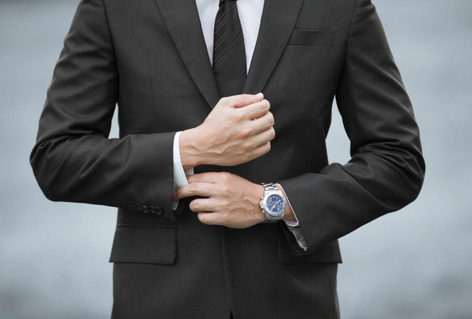Mężczyzna w garniturze z zegarkiem na ręce.